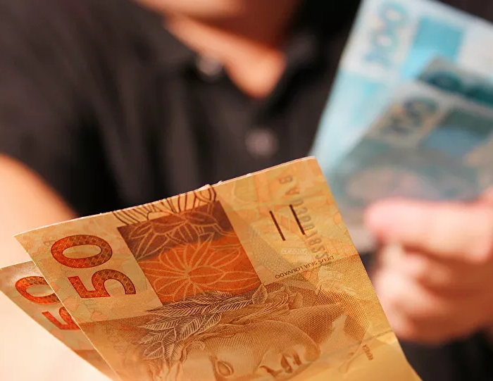 emprestimo-homem segurando dinheiro